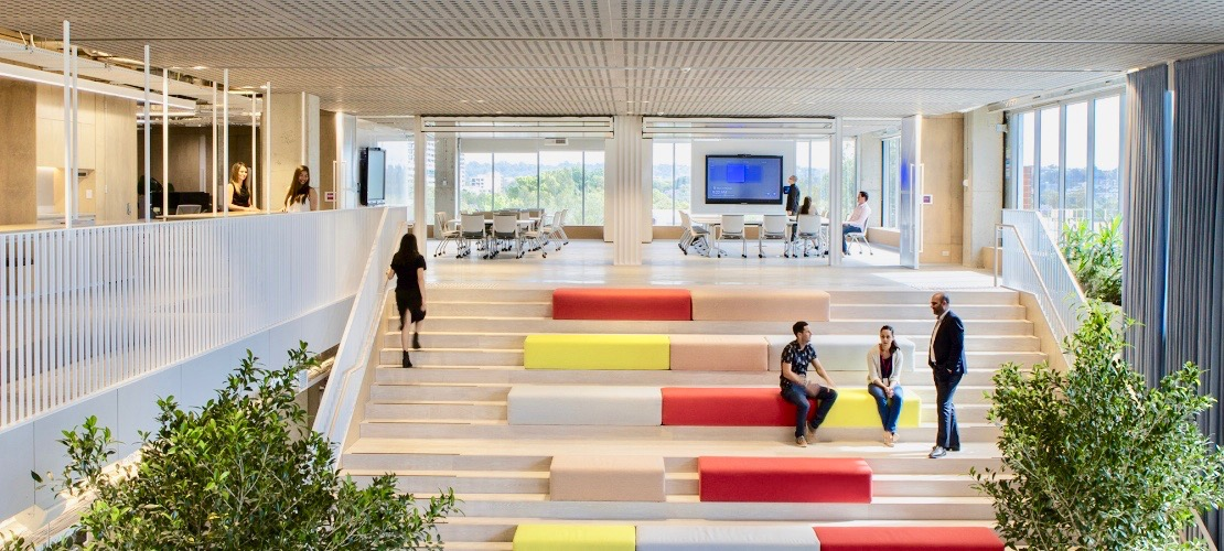 Delos Australia offices staircase with colorful seating area inside atrium