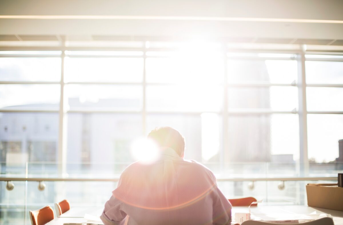 sunlight hitting the back of man working in open plan office