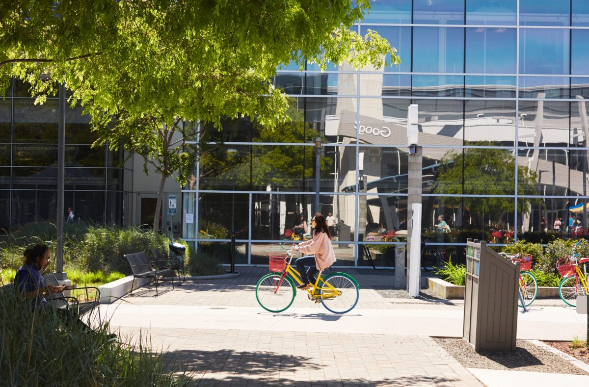 woman biking past googleplex on sunny day