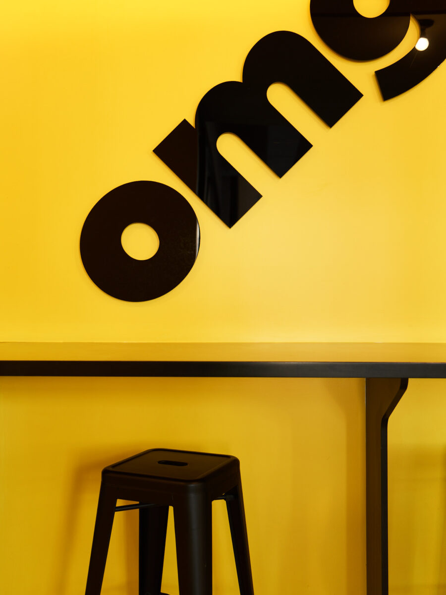 buzzfeed new york office iconic yellow omg mural with black stool